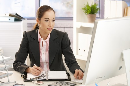 Smiling young businesswoman sitting in bright office, working with computer at desk, taking notes. photo