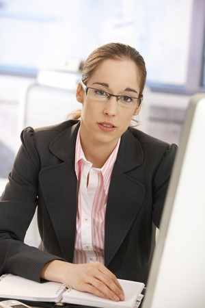 Young businesswoman wearing glasses, sitting at desk, looking at camera. photo