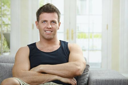 Portrait of muscular man wearing black t-hirt sitting on sofa at home, smiling. photo