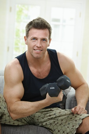 Muscular man sitting at home on sofa, doing excercise with hand barbell.