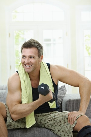 Muscular man sitting on sofa at home, doing excercise with hand barbell. Stock Photo - 7563498