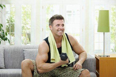 home gym: Muscular man sitting on sofa at home, doing excercise with hand barbell.
