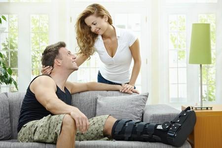 jambe cass�e: Love couple ? la maison. Homme qui se repose sa jambe cass?e sur le canap?, sa petite amie, l'embrassant par derri?re. Banque d'images