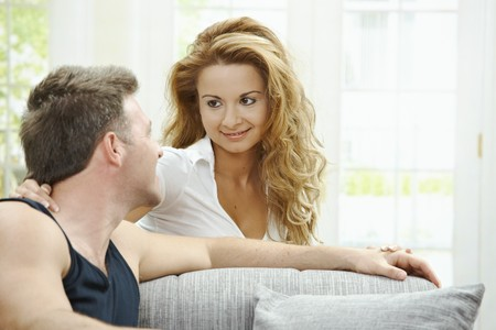 Love couple at home. Man sitting on sofa, his girlfriend embracing him from behind. photo