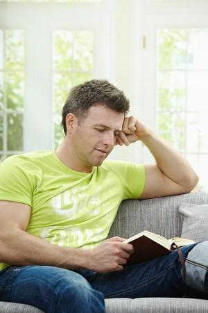 BUEN VIVIR: Casual hombre vistiendo pantalones vaqueros y camiseta sentado en el sof� en el hogar, libro de lectura.  Foto de archivo