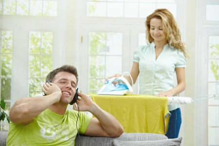 Husband sitting at couch listening music, wife ironing in the background, smiling. Selective focus on man. Stock Photo - 7563474