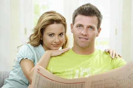 Love couple reading newspaper together on couch at home, smiling. photo