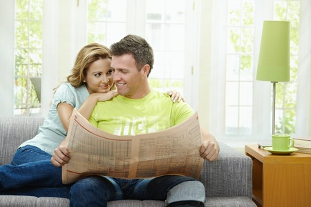 Love couple reading newspaper together on couch at home, looking at camera, smiling. photo