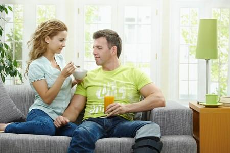 BUEN VIVIR: Pareja de amor comer cereales de desayuno juntos, sentado en el sof� en casa.  Foto de archivo