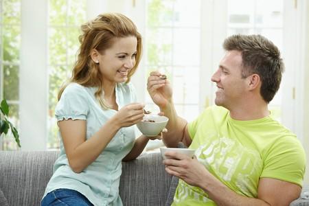pareja comiendo: Pareja de amor comer cereales de desayuno juntos, sentado en el sof� en casa.  Foto de archivo