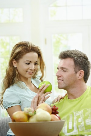 Love couple having breakfast together. Woman giving apple to her boyfriend. Stock Photo - 7563480