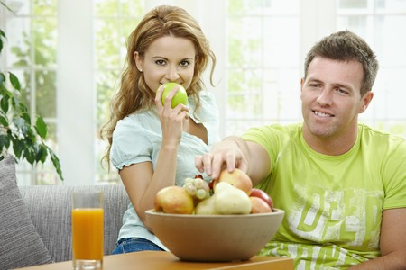 Love couple having breakfast together, holding apples, looking at camera smiling. photo
