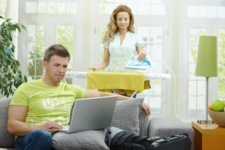 BUEN VIVIR: Hombre con la pierna rota, descansando sobre el sof�, equipo port�til. Mujer haciendo planchado en segundo plano.  Foto de archivo