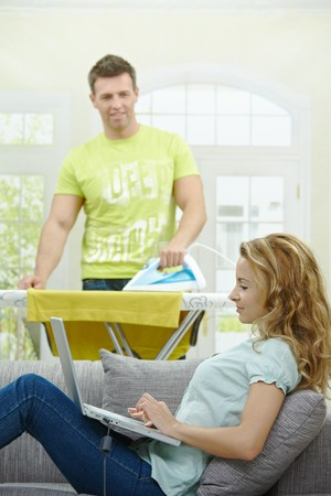 Wife sitting on couch using laptop, husband ironing in the background, smiling. Selective focus on man. Stock Photo - 7563493