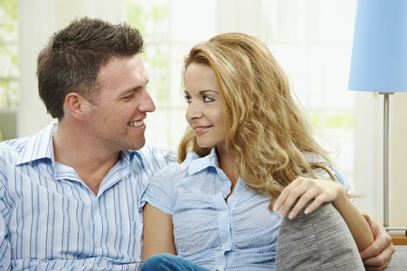 Portrait of happy couple sitting on sofa embracing, looking at camera and smiling.  photo