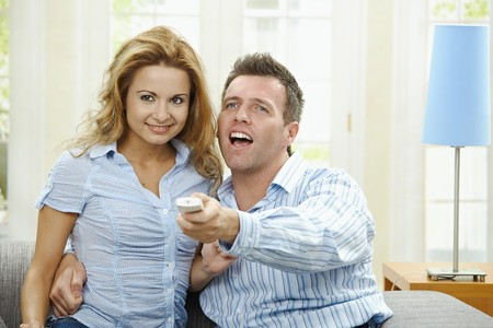 Excited couple watching TV at home, sitting on couch, holding remote control in hand. photo
