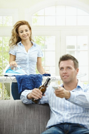 Happy man sitting at couch watching TV, woman ironing in the background. Selective focus on man. Stock Photo - 7563478