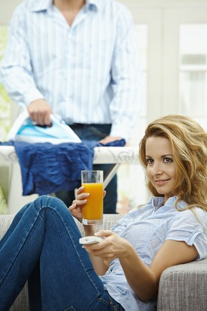 Happy woman sitting at couch watching TV, man ironing in the background. Selective focus on woman. Stock Photo - 7563495