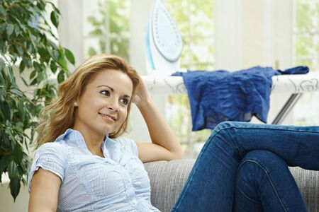 Tired young woman resting on couch, having a break during housework. Stock Photo - 7563519