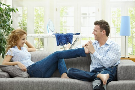 Couple relaxing at home on sofa, man giving foot massage to her gildfriend. photo