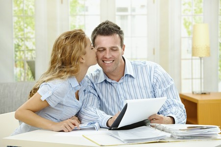 Happy couple sitting at home, planning household financials. photo