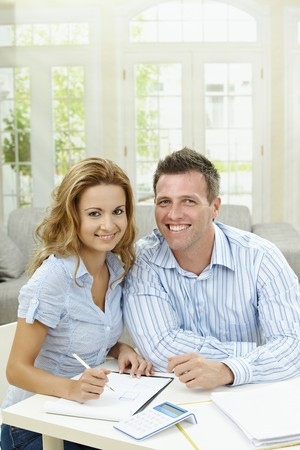 Happy couple sitting at home, planning with paper and calculator. photo