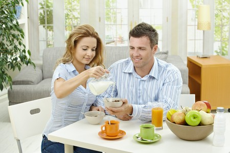 Couple having healty breakfast at home, eating cereals, fruits and drinking orange juice. photo