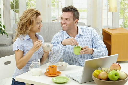 Couple having healthy breakfast at home, eating cereals drinking coffee, and looking at laptop computer. photo
