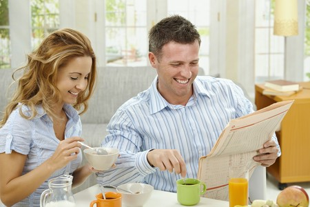 Couple having healthy breakfast at home, eating cereals drinking coffee, and reading newspaper. photo