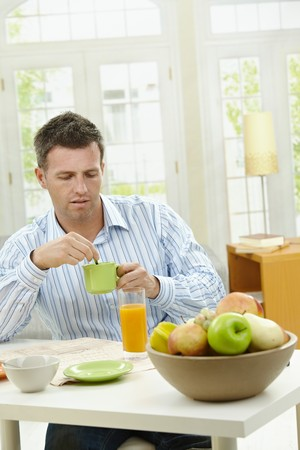 Young man having healthy breakfast, drinking coffee, orange juice and reading newspaper. photo