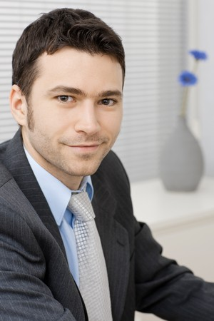 Portrait of happy smiling young businessman at office. Stock Photo - 7601576