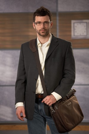 Portrait of young professional wearing stylish clothes and glasses, holding laptop computer bag, looking at camera. photo