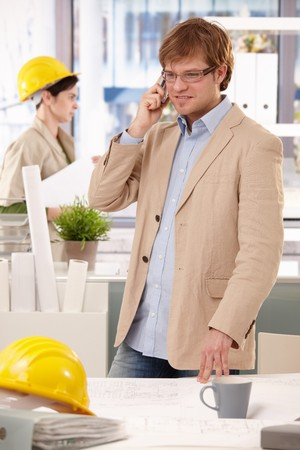 Young architect standing at office desk, talking on mobile phone. photo