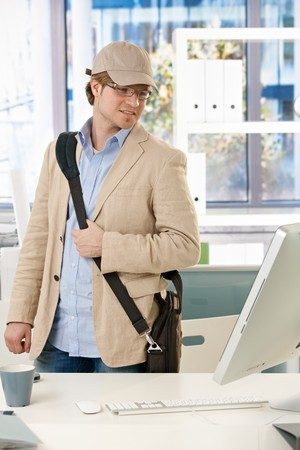 Young businessman wearing laptop bag leaving office, looking back to screen on desk. photo