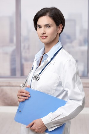 Portrait of attractive female doctor holding clipboard indoor, smiling. Stock Photo - 7601569