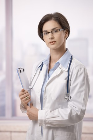 Portrait of attractive female doctor holding clipboard and glasses indoor, looking at camera. Stock Photo - 7601552