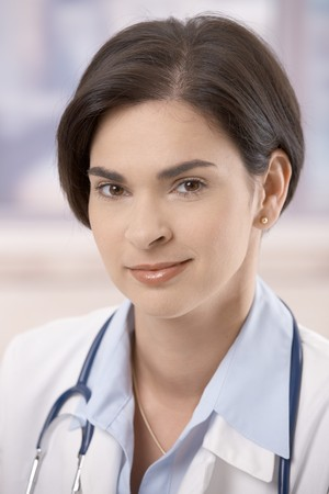 Closeup portrait of attractive young female doctor looking at camera, smiling. Stock Photo - 7601584
