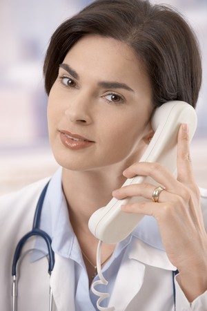 Attractive mid-adult caucasian female doctor talking on landline phone, looking at camera. photo