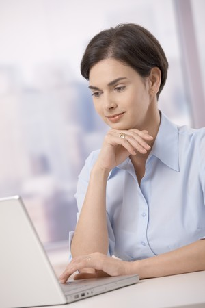 Mid adult businesswoman sitting at skyscraper office table working on laptop computer, smiling. photo