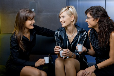 Group of happy young businesswomen sitting on couch in office lobby, drinking coffee, talking.