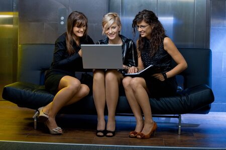 Team of happy young businesswoman having a meeting, using laptop computer, smiling. photo