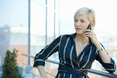officetower: Young businesswoman talking on mobile phone, outdoor.