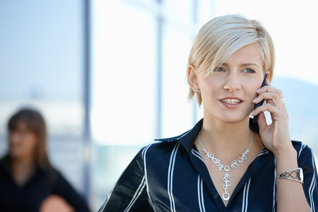 officetower: Young businesswoman talking on mobile phone, outside office building. Stock Photo