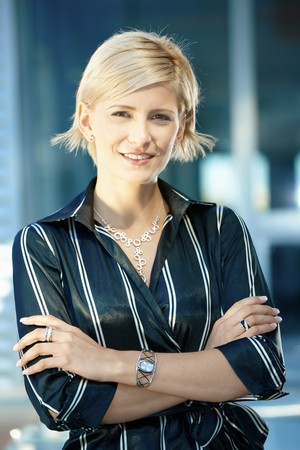 officetower: Portrait of attractive young businesswoman standing arms crossed, smiling.