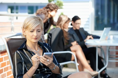 cell phone tower: Young businesswoman using smart mobile phone, outside office building.