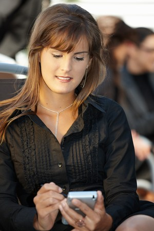 officetower: Businesswoman giovani seduti in poltrona, utilizzando smart phone.