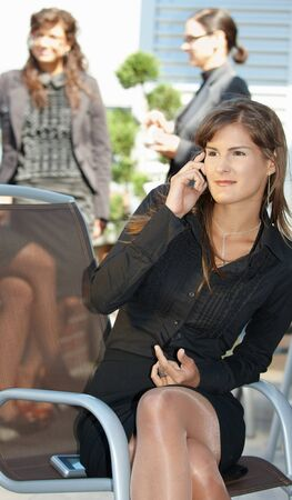 officetower: Young businesswoman talking on mobile phone, outdoors.