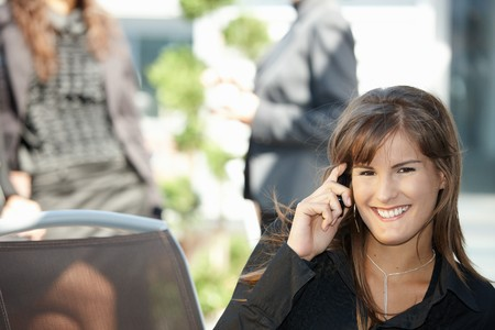 Young businesswoman talking on mobile phone, outdoors. photo