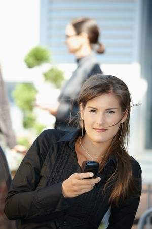 officetower: Young businesswoman using mobile phone, outdoors.