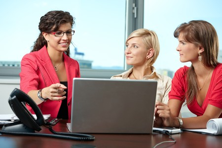 collaborating: Young businesswomen sitting at table in meeting room, using laptop computer, smiling. Stock Photo